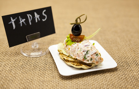 excellent background: Fresh Spanish tapas on bread baguette smoked Norwegian salmon with black olive butter, herbs and onions. An excellent background for the menus, the restaurant, the Cafe Mediterranean cuisine TAPAS poster . Stock Photo