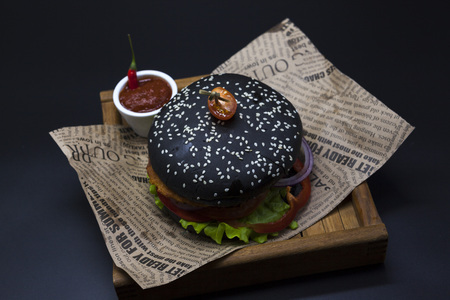 fused: Black burger. A burger with a black roll slices of juicy marble beef, fused cheese, fresh salad and sauce of a barbecue. A burger on the newspaper on a wooden tray  on a dark background Stock Photo