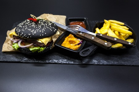fused: Black burger. Set of the black burger. Stone plate with: black burger roll slices of juicy marble beef, fused cheese, fresh salad with French fries on a cast-iron griddle, with chili sauce and guakomole.