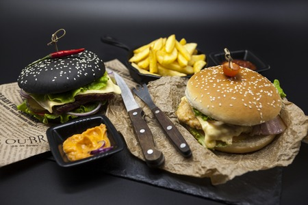 fused: Set of the black burger and classical American burger . Black burger roll slices of juicy marble beef, fused cheese, fresh salad with French fries on a cast-iron griddle, with chili sauce and guakomole, classical juicy burger with chicken and ham on a woo