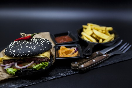 french roll: Black burger. Set of the black burger. Stone plate with: black burger roll slices of juicy marble beef, fused cheese, fresh salad with French fries on a cast-iron griddle, with chili sauce and guakomole.