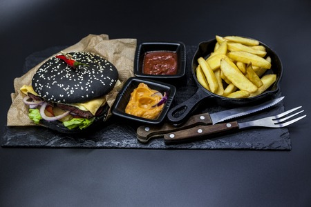 griddle: Black burger. Set of the black burger. Stone plate with: black burger roll slices of juicy marble beef, fused cheese, fresh salad with French fries on a cast-iron griddle, with chili sauce and guakomole.