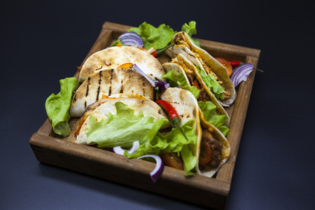 tex mex: Mexican Tortilla with meat, beef and stewed vegetables and spicy sauce on a wooden tray