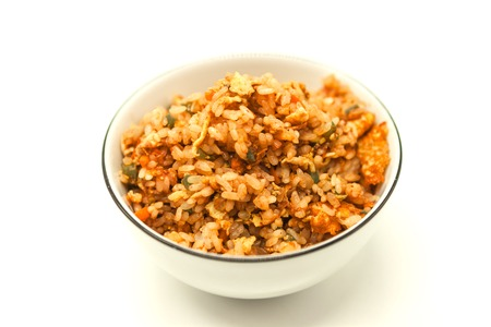 the favourite: Fried Chinese rice with vegetables and egg, in a bowl on a white background. Chinese favourite garnish