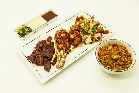 arroz chino: Mar y tierra, langosta frita y jugosa participaci�n con una guarnici�n de verduras fritas con arroz chino frito y salsas picantes Foto de archivo