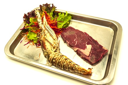stake: Set for surf and turf a fresh crude lobster and a juicy piece of a marble stake on a tray Stock Photo