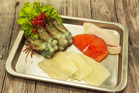 silver tray: Fresh seafood on a silver tray: tiger shrimps, squids, salmon, cod