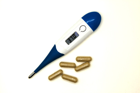 old mercury: Modern electronic thermometer with pills closeup on white background.