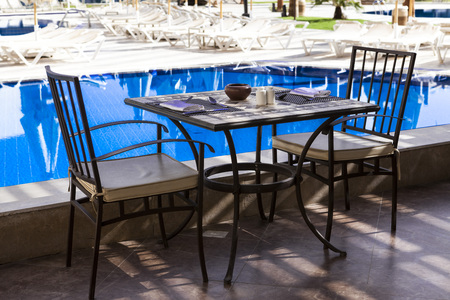 necking: Table and chairs by the pool, Breakfast in Ibiza. The morning after a fun party