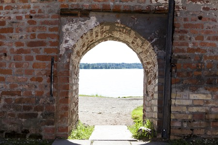excellent background: Open the door on the stone wall of the fortress castle overlooking the lake. Excellent background
