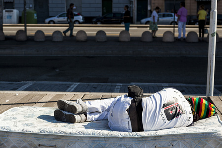 impoverished: A homeless black man asleep on the old sofa in the street. Stock Photo