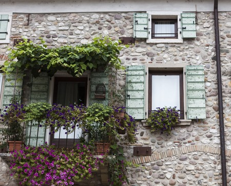 Old window with open shutters with flowers on the window sill on the stone wall. Italian Village.