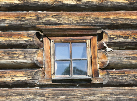 eldest: Small Old window with glass with a blue sky on the background of the wooden wall of the countryside log house. Stock Photo
