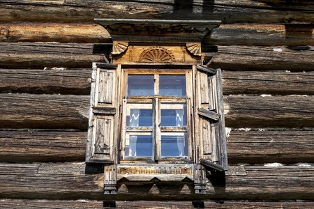 eldest: Old window with open shutters glass with a blue sky on the background of the wooden wall of the countryside log house.