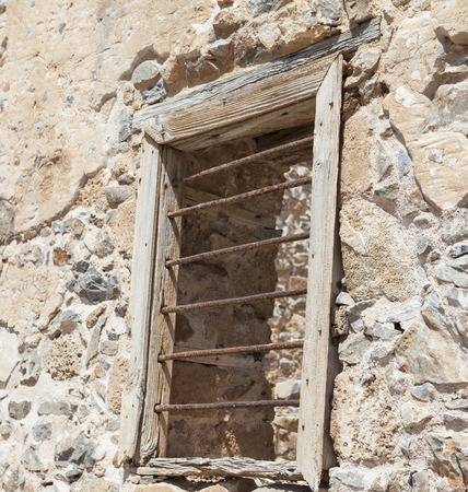 evildoer: The ruins, the ruins of the destroyed castle fortress wall with a window with iron bars. The wall of the old prison window with bars on the escape of criminals