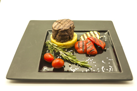 fried potatoes: Mignon steak with fried potatoes and grilled vegetables on a beautiful black plate on a white background