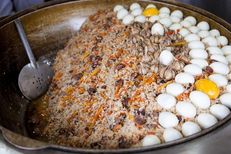 Traditional Asian pilaf with beef and chicken eggs. A large cauldron, rice devzira, cumin spices, cotton seed oil. The famous dish of the East