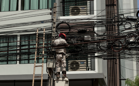 essentially: Electric.Working man repairs an electrical malfunction in the wiring. Thailand Bangkok.
