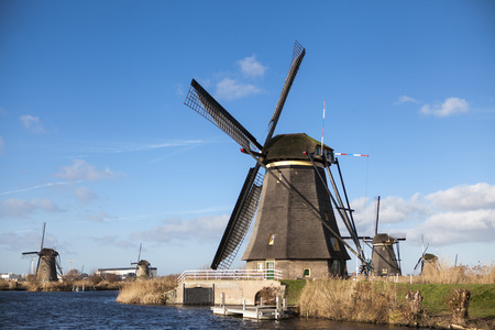 river banks: Old windmill stands on the banks of the canal, and water pumps. White clouds on a blue sky, the wind is blowing. Holland windmill on a canal. Old mill chalk and flour . The beautiful backdrop of the countryside of Holland.Traditional dutch windmill near t