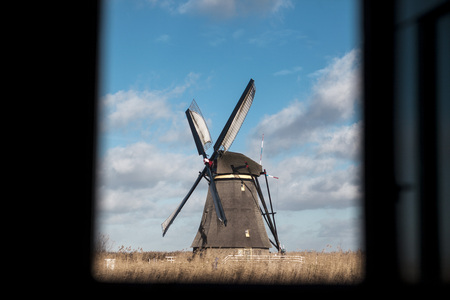 watermill: An unusual perspective photo made from the window of the house, beautiful dark frame with a perspective window.Traditional dutch windmill near the canal. Netherlands. Old windmill stands on the banks of the canal, and water pumps. White clouds on a blue s