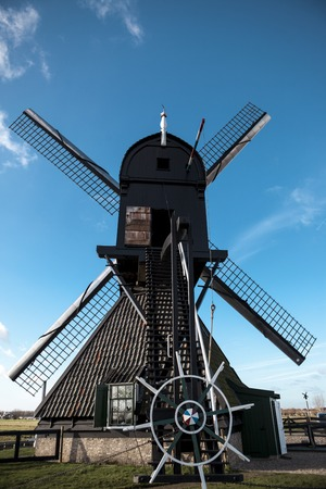watermill: Dutch windmill, rear view, large blades, the steering wheel controls. The mill is on the canals of Holland near the city RotterdamTraditional dutch windmill near the canal. Netherlands. Old windmill stands on the banks of the canal, and water pumps. White Stock Photo