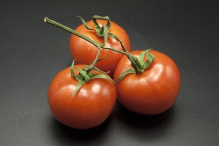 Ripe tomatoes on black background. Stock Photo
