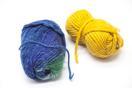 Green blue and  yellow ball of wool yarn for knitting close up on a white background.