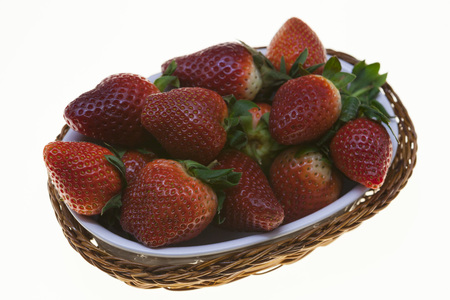 vitamine: Juicy berries of ripe strawberries in a wicker basket on a white background Stock Photo