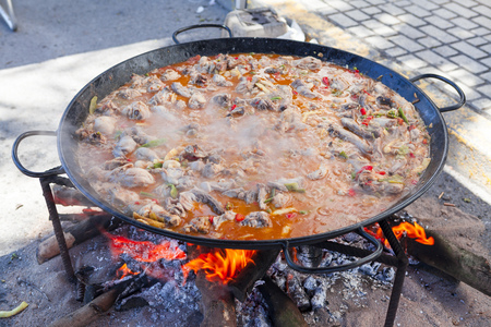Paella. The national Spanish dish of paella in a large skillet is cooked on an open fire, at the stake. Stok Fotoğraf