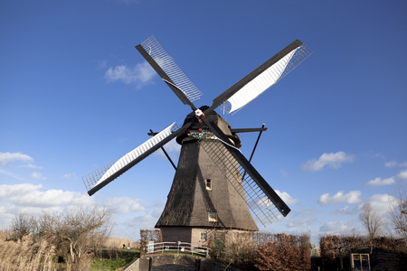 watermill: The old Dutch windmills, Holland, rural expanses . Windmills, the symbol of Holland. Holland windmill on a canal. Old mill chalk and flour . The beautiful backdrop of the countryside of Holland.Traditional dutch windmill near the canal. Netherlands. Old w Stock Photo