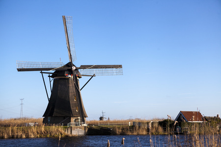 The old Dutch windmills, Holland, rural expanses . Windmills, the symbol of Holland. Holland windmill on a canal. Old mill chalk and flour . Stock Photo