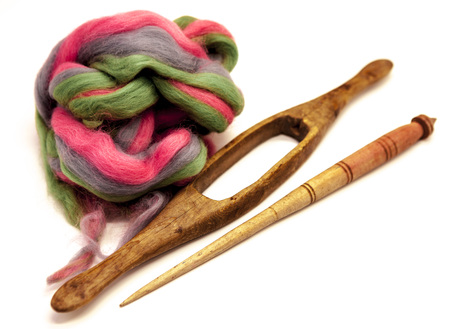 Washed Angora wool for felting or knitting. The distaff and spindle closeup on a white background