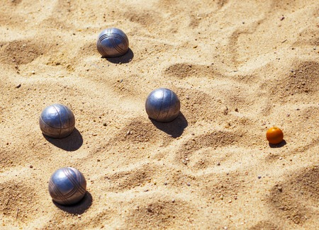 Metal bowls for playing petanque and a small wood jack