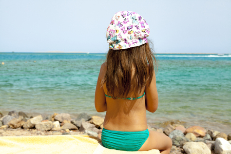 Little girl is sitting on the beach. Stock Photo
