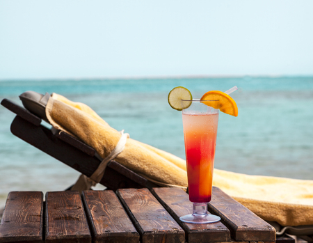 A glass goblet with a cocktail on a deckchair on the beach Stock Photo