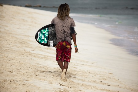 Surfing. A young man is a surfer with a Board on a sandy beach. Cape Verde.