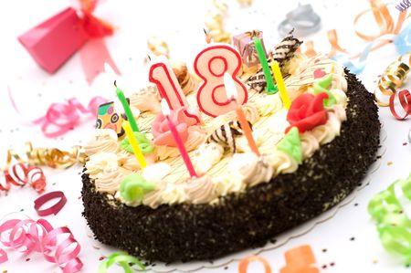 torta de cumpleaños para 18 años de aniversario rodeado de serpentinas y cajas de regalo en el fondo blanco Foto de archivo - 3530403