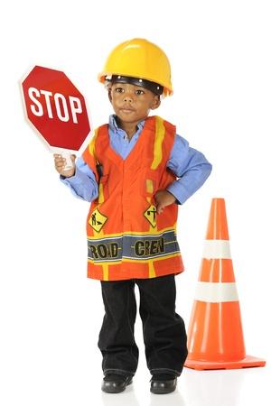 """ni�os sosteniendo un cartel: Un adorable preescolar """"camino de miembro de la tripulaci�n"""", en un chaleco de seguridad y casco, sosteniendo en alto una se�al de stop. Aislado en blanco."""