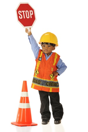 A serious little boy in road crew gear holding a stop sign high.  Isolated on white.