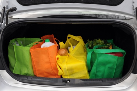 Four colorful eco-friendly shopping bags filled mostly with groceries in the trunk of a car  Stock Photo