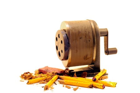Vintage manual-crank pencil sharpener surrounded by broken pencils, shavings and an eraser   Isolated on white  photo