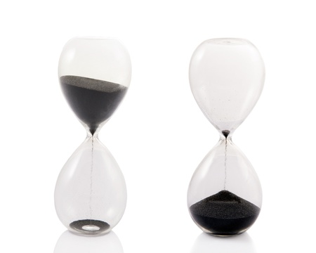 ends: A totally clear hourglass in two stages  as the black sand begins to fall and as it ends   Isolated on white