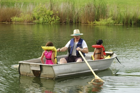A senior man paddling a small boat with his two young grandchildren  photo