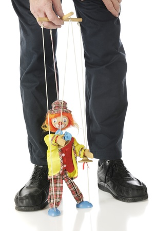 A clown marionette performing between the legs and under the hand of a puppet master   Isolated on white