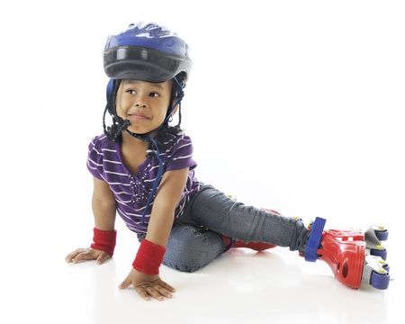An adorable preschooler smiling though fallen while learning to roller skate   On a white background