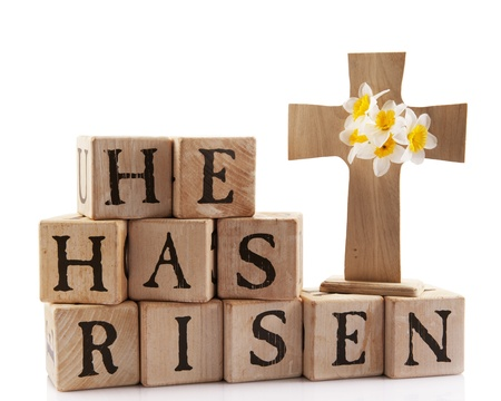 easter flowers: A wooden cross with the words spelled out with rustic alphabet blocks.  Isolated on white.