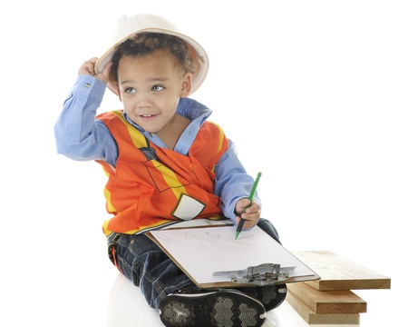 An adorable 2-year-old wiring on a clip board in his construction garb   On a white background  Stock Photo - 13974864