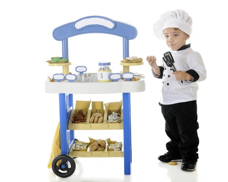 goodies: A preschool boy, becoming stupified from snitching goodies from his vendor stand.  The stands signs left blank for your text.  On a white background. Stock Photo