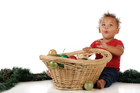 An adorable toddler delighted with a basketful of Christmas bulbs.  One a white background. photo