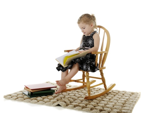 An adorable preschooler seriously enjoying books her her child-sized rocker.  On a white background. photo